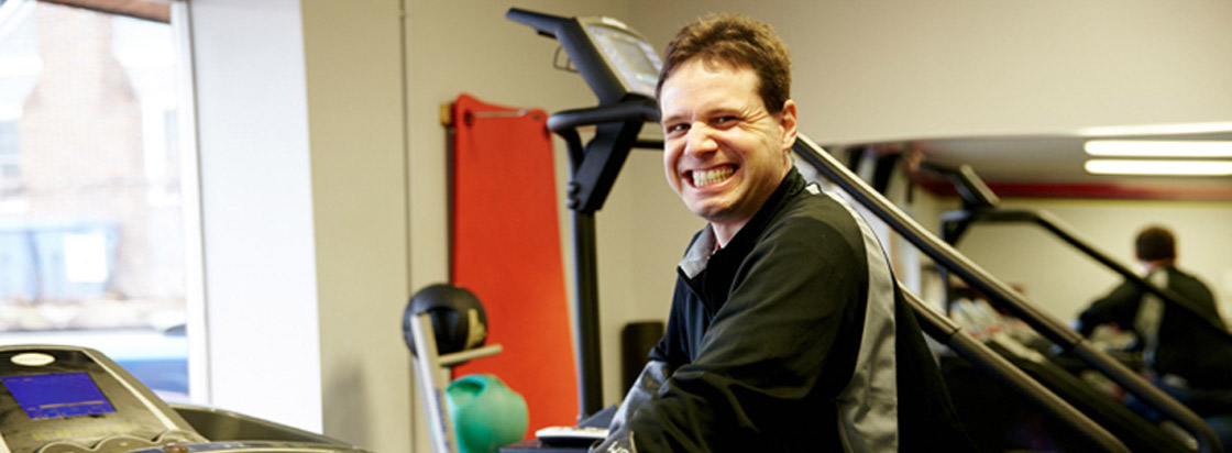 ticket to work guy at gym smiling on treadmill